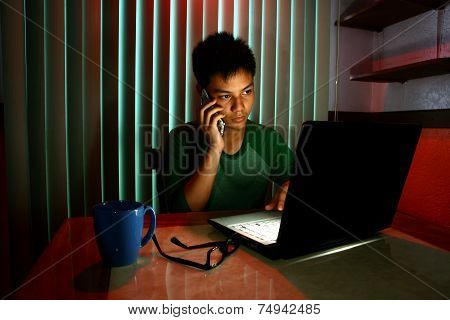 Young Teen using a cellphone or smartphone in front of a laptop computer