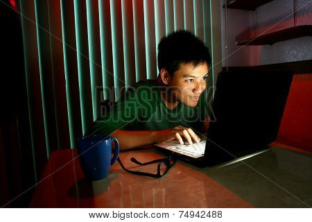 Young Teen with eyeglasses in front of a laptop computer