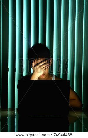 Young Teen in front of a laptop computer and covering his eyes