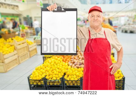 Mature market vendor holding a clipboard in front of an aisle with fruits and vegetables