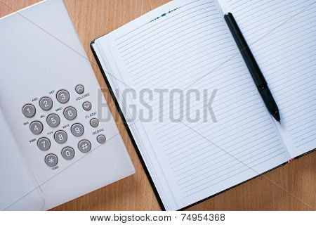Clean Notebook, Pen And Telephone On Desk