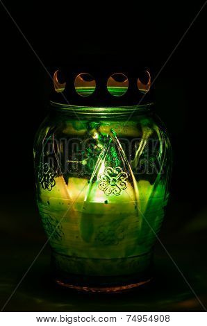 Green Burning Votive Candle In The Dark