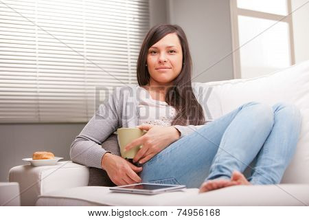 Relaxed Woman Having Breakfast In Living Room