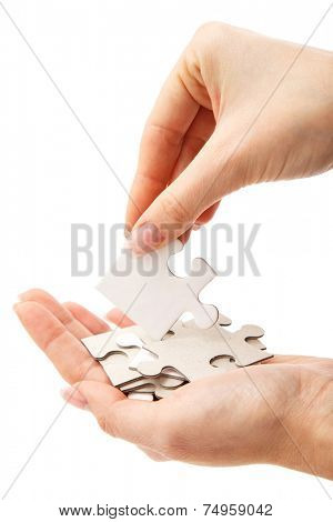 Girl holding white puzzle on a white background