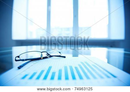 Eyeglasses and business document on workplace
