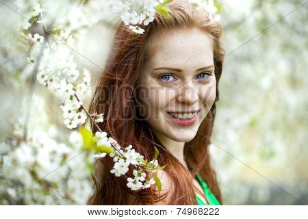 Spring beauty girl with long red blowing hair outdoors. Blooming trees. Romantic young woman portrait