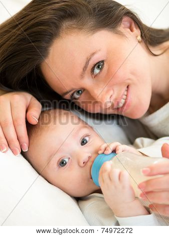 mother feeding kid boy with a milk bottle at home
