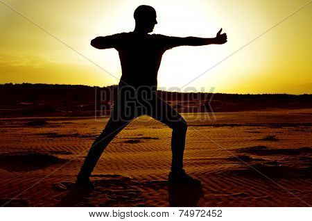 a young man practicing the yoga archer pose in backlight at sunset