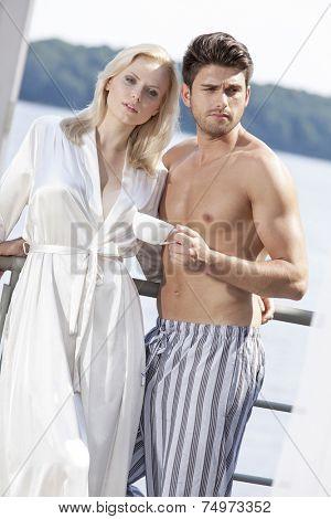 Young couple in sleepwear having coffee on hotel balcony