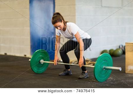 Full length of young woman lifting barbell at gym