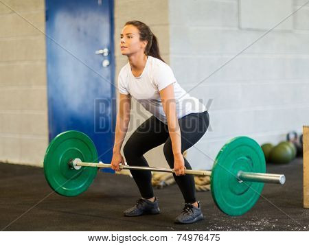 Full length of young woman lifting barbell in gym
