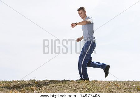 Full length of man checking time while jogging against sky
