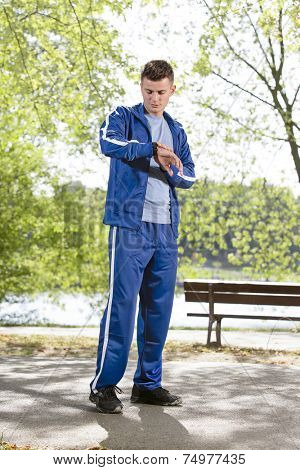 Full length of fit man checking time on path in park