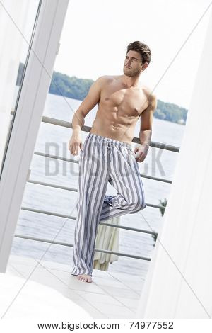 Full length of handsome young man leaning on hotel balcony looking away