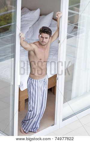 Full length of thoughtful young man in pajama standing at balcony doorway