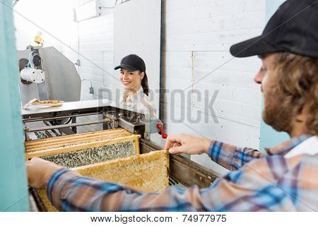 Portrait of happy young female beekeeper standing with colleague working in beekeeping factory