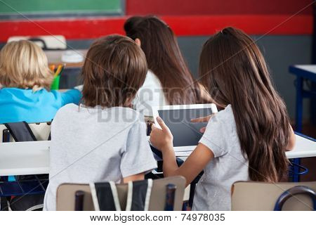 Rear view of little schoolgirl using digital tablet with boy at desk in classroom