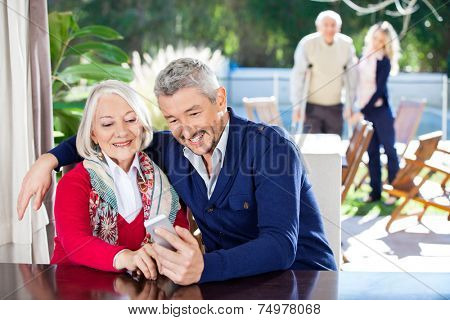 Smiling grandson and grandmother using smartphone with family in background at nursing home