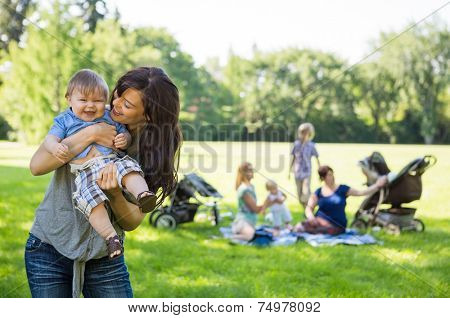 Mother carrying cheerful baby boy with friends and children in background at park