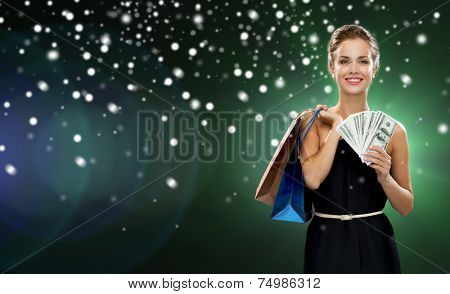 people, sale, gifts, money and holidays concept - smiling woman in dress with shopping bags and money over snow and night lights background