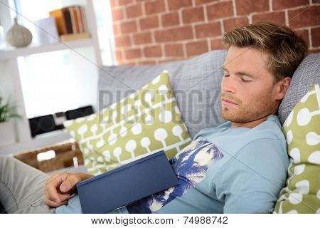 Young man at home taking a nap in sofa