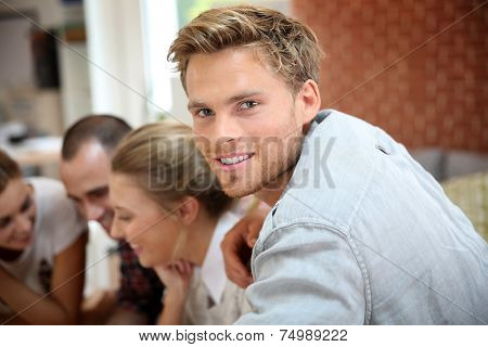 Portrait of handsome guy amongst group of friends