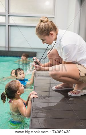 Pretty swimming coach showing boy his time at the leisure center