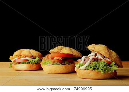 Three tasty burgers on wooden board