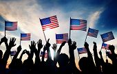 foto of waving  - Group of People Waving American Flags at Sunset - JPG