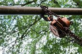 picture of pulley  - Orange Industrial hook chains attached to a pulley and Green tree background - JPG