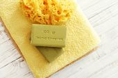 stock photo of bath sponge  - Greek olive soap with bath towels and bath sponge on wooden background - JPG