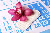 pic of menses  - Sanitary pad and lilac orchid on blue calendar background - JPG