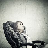 stock photo of up-skirt  - Young confident businesswoman sitting in chair with legs up - JPG