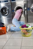 pic of laundromat  - Young woman searching clothes in washing machine drum at laundromat - JPG