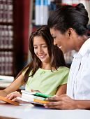 stock photo of librarian  - Happy female librarian and schoolgirl looking together at book in library - JPG