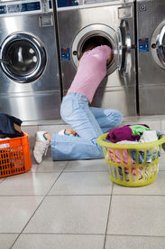 stock photo of laundromat  - Young woman searching clothes in washing machine drum at laundromat - JPG