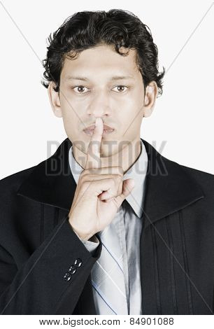 Businessman with his fingers on his lips