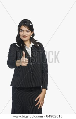 Confident businesswoman showing thumbs-up
