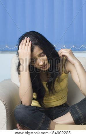 Young woman sitting on a couch with her head in her hand
