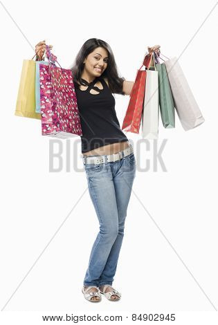 Portrait of a young woman holding shopping bags