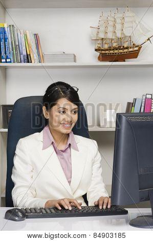 Businesswoman working on a desktop PC in an office