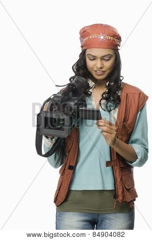 Female videographer looking at video camera