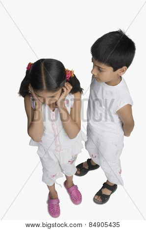Girl covering her ears while her brother talking