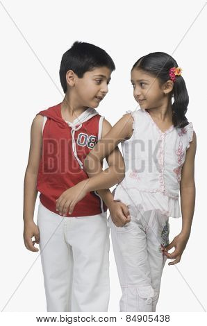 Two children looking at each other with their arm in arm