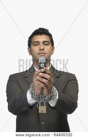 Businessman looking at a mobile phone with his hands in chains