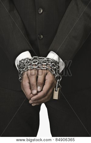 Close-up of a businessman's hands locked with chains
