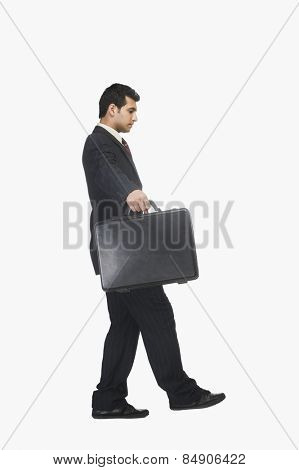 Businessman walking carefully with a briefcase