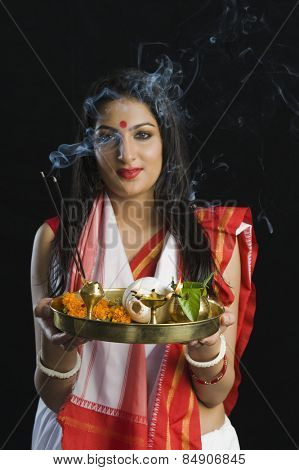 Beautiful woman in a Bengali sari holding pooja thali