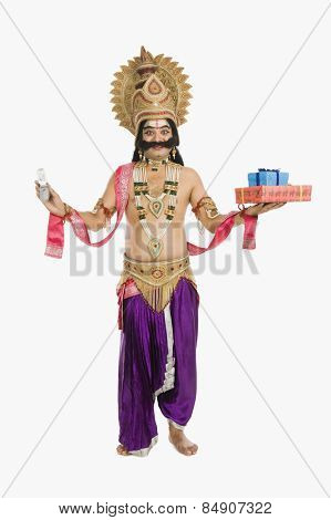 Indian man dressed-up as Ravana holding mobile phone and gifts