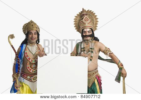 Two men dressed-up as Rama and Ravana and holding a blank placard